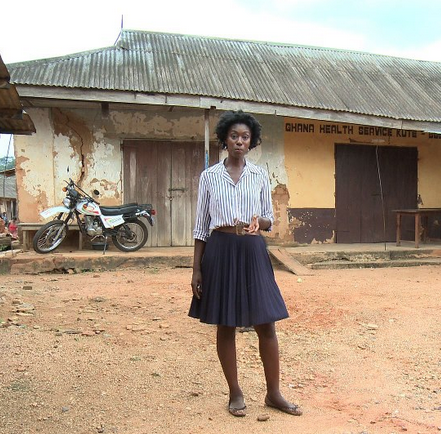 Maternal Health Channel host Ivy in front of the government clinic in Kute Buem.